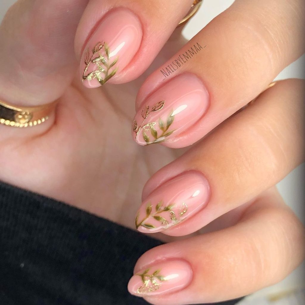 green and gold leaves on neutral color nails with almond shape
