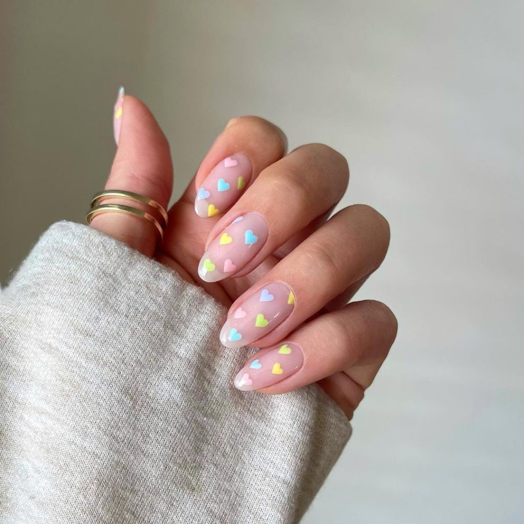 timy colorful heart shape on spring nails with almond shape