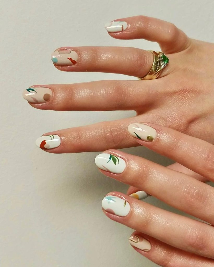 colorful leafs on creamy short nails with almond shape