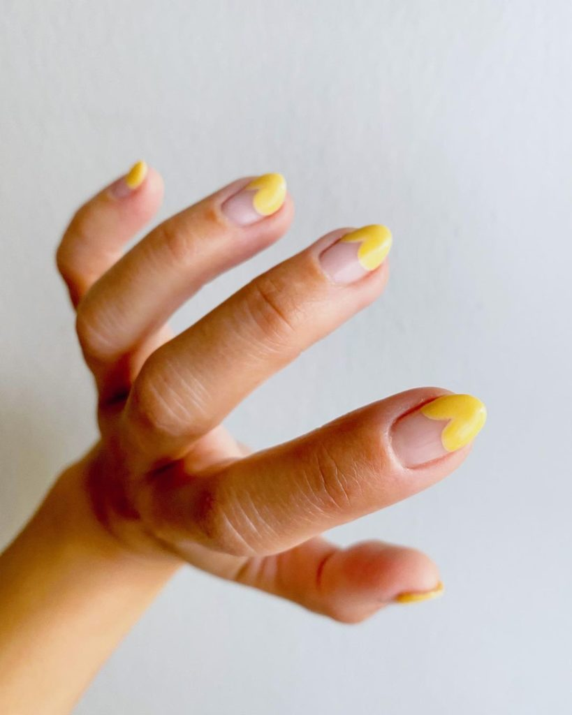 french tips with yellow heart design on almond shaped short nails